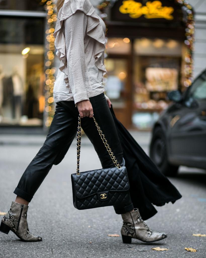 beigen Rüschenbluse, normalen schwarzen Lederhose , Python Print Boots, schwarzen Chanel Tasche, überlangen Mantel