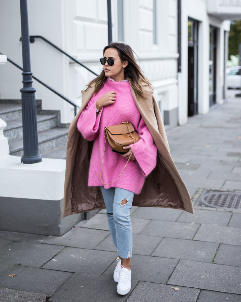 huge oversize pink knit with casual jeans, white sneakers and a long caramel colored coat