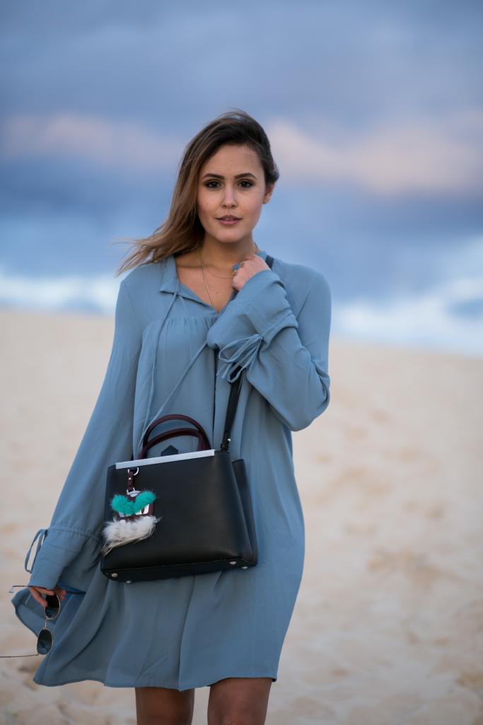 Strandbild - blaues Kleid, Tasche, Sonnenbrille