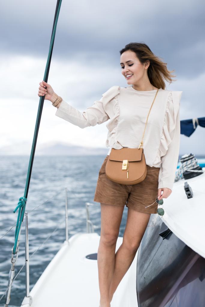 Bild auf Schiff - beige Pullover, kurze Hose, Tasche, Sonnenbrille