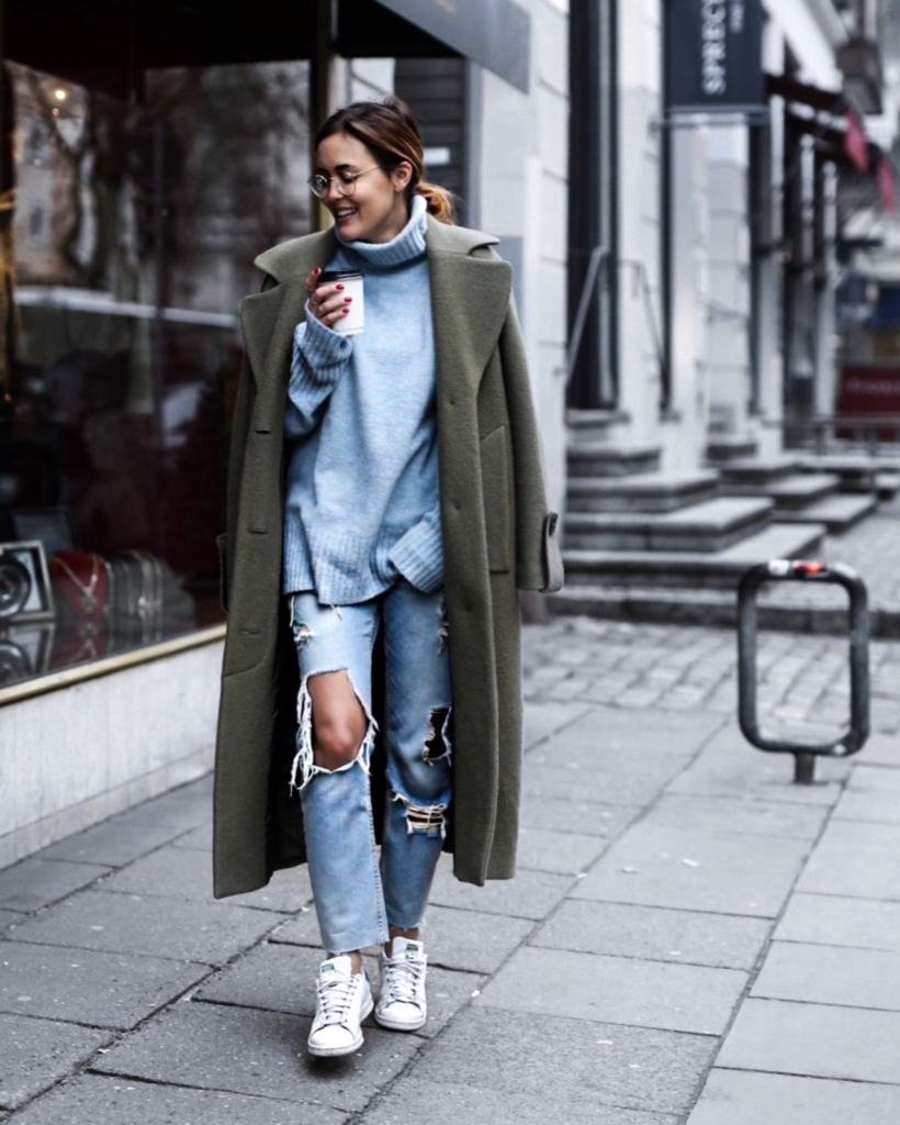 olive Mantel, Jeans, Pullover, Sneaker, Brille