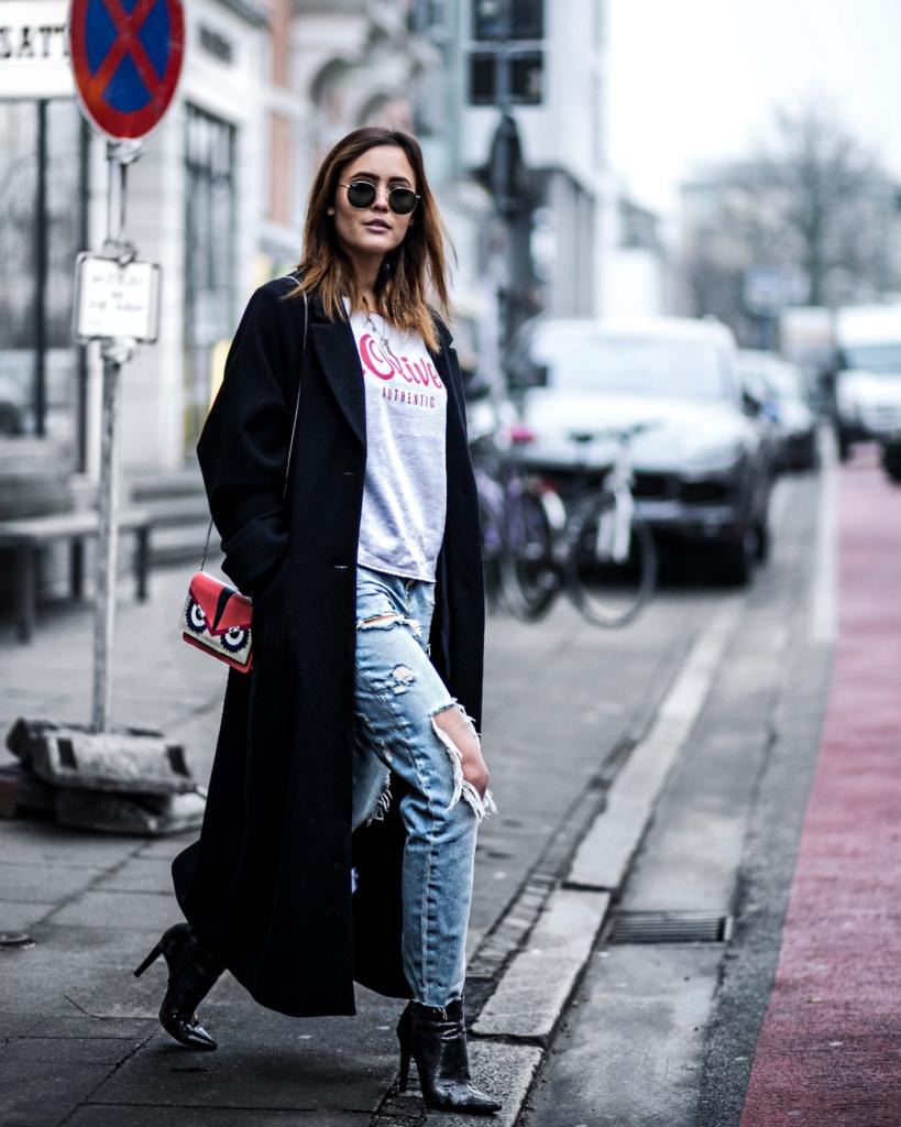 Printshirt, Sonnenbrille, Tasche, langer Mantel, Stiefeletten, Jeans