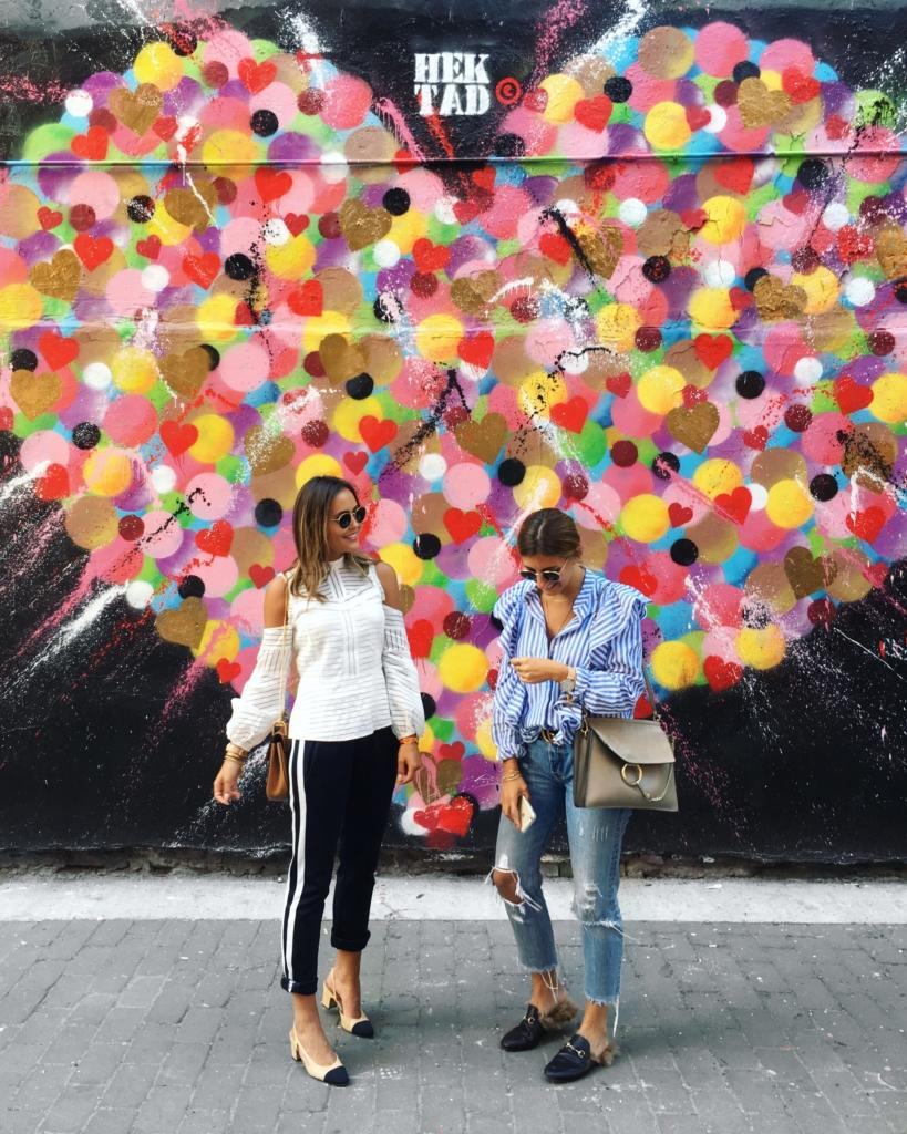 Bild vor Kunstwerk, Jogginhose, Pumps, Bluse, Sonnenbrille