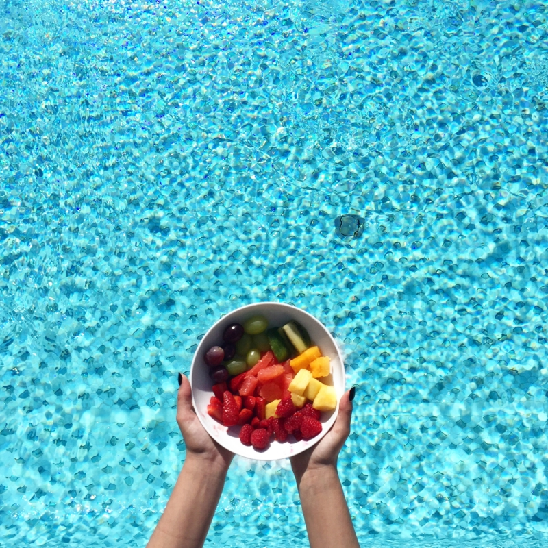 bunter Obstsalat vor blauem Poolwasser