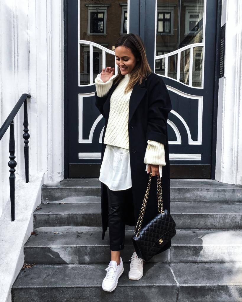 weißer Strickpullover, schwarzer Mantel und Chanel Tasche