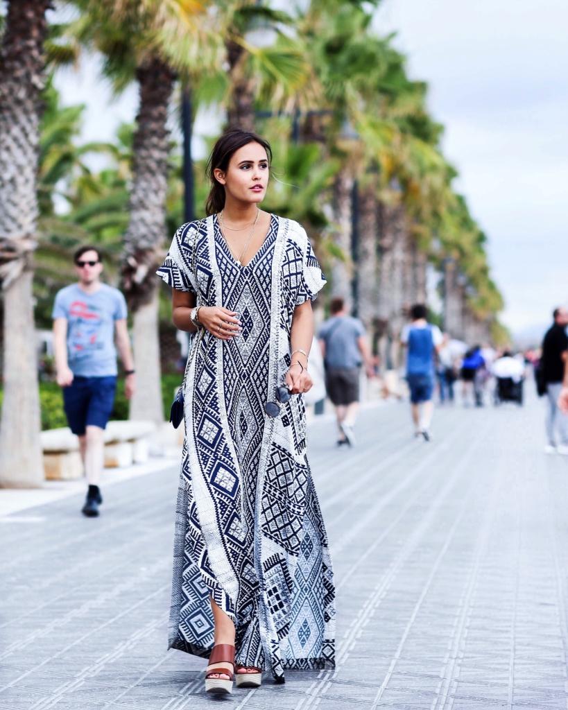 schwarz weißer Poncho, Sonnenbrille an Strandpromenade