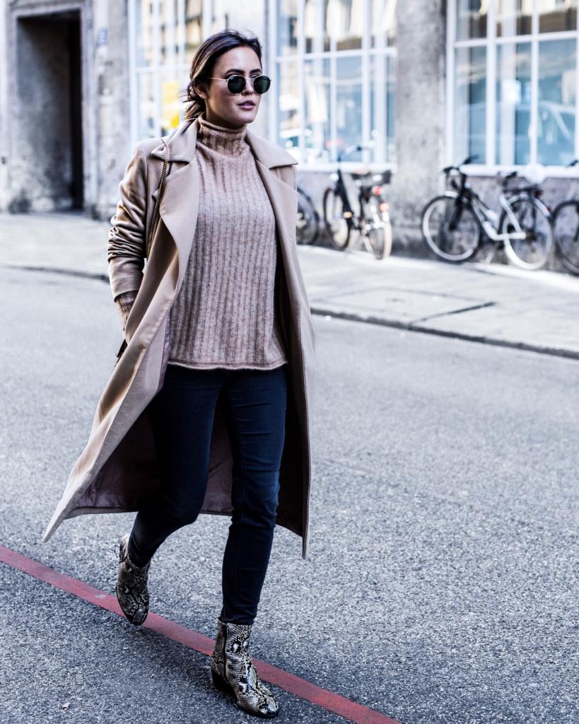 brauner Mantel, brauner Strickpullover, Jeans, Stiefeletten, Sonnenbrille