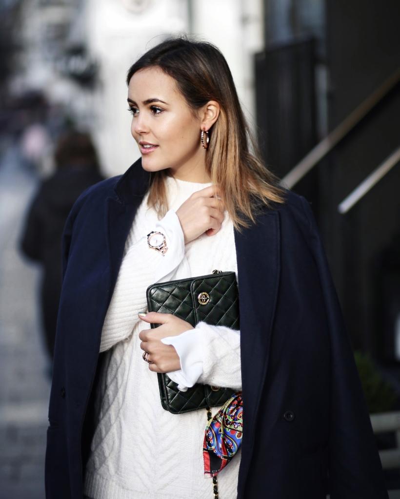 blauer Mantel, weißer Strickpullover, Tasche